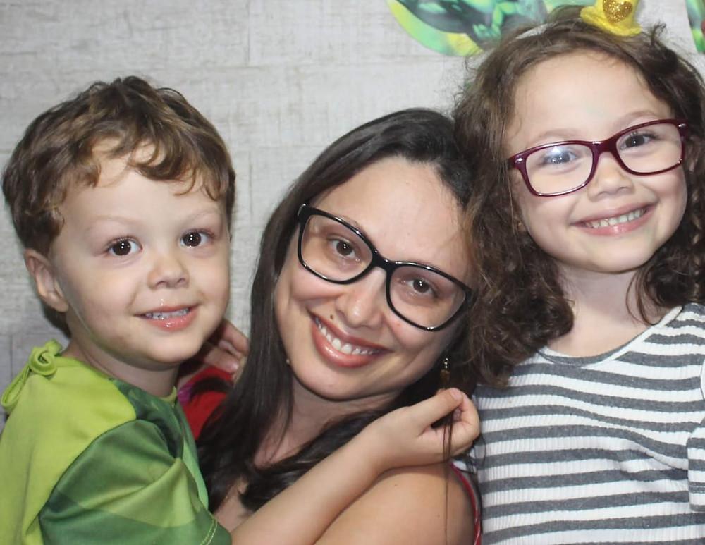 Juliana está de óculos, sorrindo e segurando Saulo no colo. Ao lado dela está Lívia, também de óculos, com fitas verdes no cabelo, uma camiseta listrada