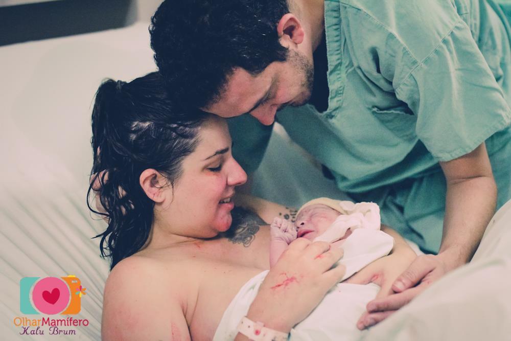 Mãe deitada com recém-nascido no colo, após o parto, e sendo amparada pelo pai do bebê