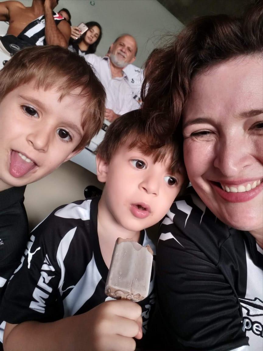A mãe, Bárbara, com os filhos Felipe e Rafael. Um dos meninos mostra a língua, e o outro segura um picolé de chocolate. Os três estão em uma arquibancada, vestindo camisas do Atlético Mineiro