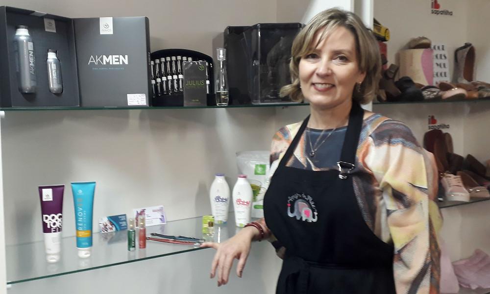 Juliane sorri diante da prateleira de cosméticos