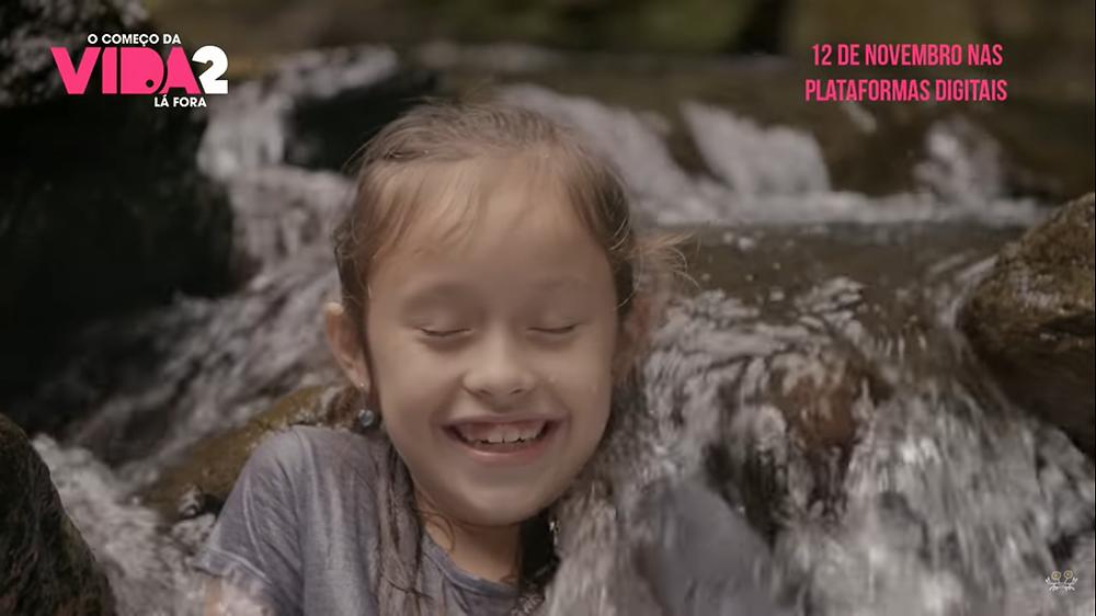 Cena do filme em que uma menina sorri de olhos fechados ao se molhar em uma queda d'água