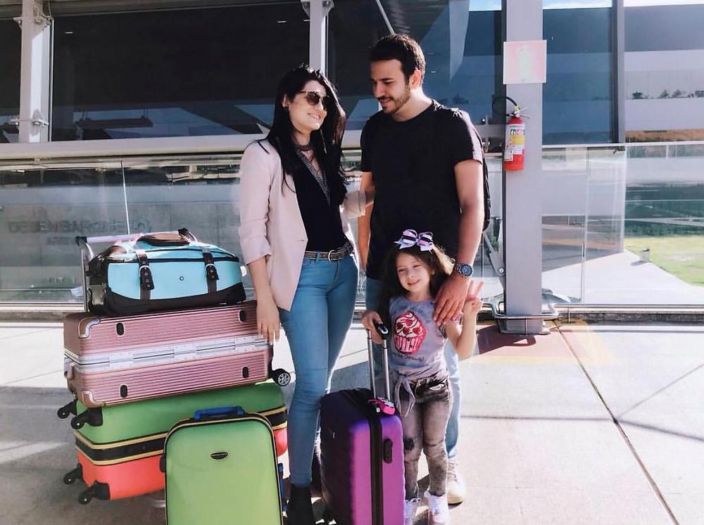 Cristina, Alexandre e Malu estão no aeroporto, rodeados por cinco malas