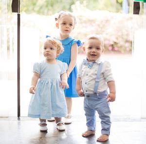 Bia está ayrás, os gêmeos estão na frente. Bia e Laura usam vestidos azuis e sapatos brancos. Gabriel usa camisa branca, calça azul, suspensório azul e gravata borboleta. Só Gabriel sorri e olha para a foto