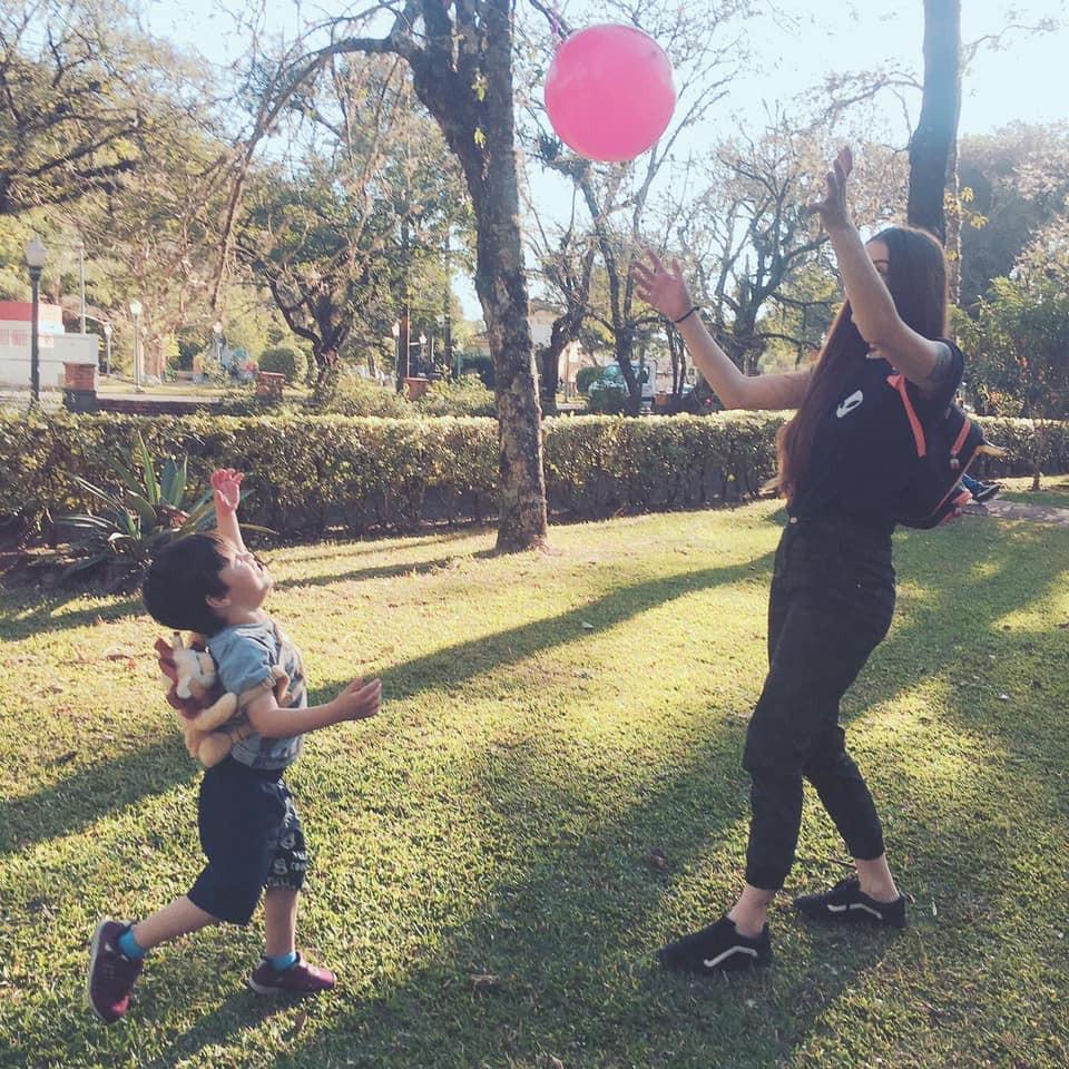 Amanda e Bernardo brincam de bola na grama