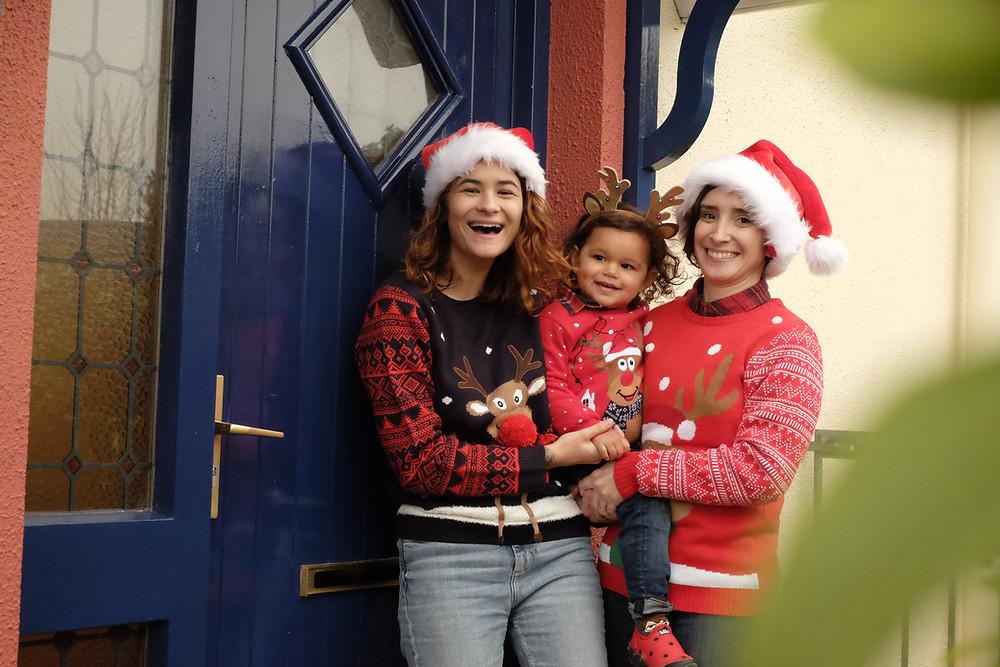 Danny e Mariel seguram Mia no colo. As três usam suéteres de rena. As mães estão de gorro de papai noel e Mia usa uma tiara de rena