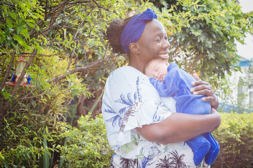 Na frente de um jardim com árvores e arbustos, Liliane segura Benício no colo. O bebê dorme tranquilo, e ela sorri repousando suavemente o rosto sobre a cabecinha do bebê