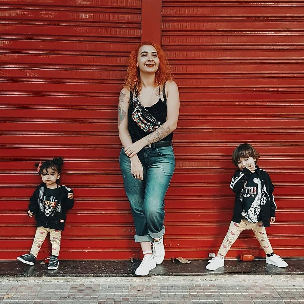 Débora está ao centro, à frente de uma porta comercial vermelha. à direita dela está Amélia, de legging e casaco preto. à esquerda está Victor, usando roupa igual à da irmã