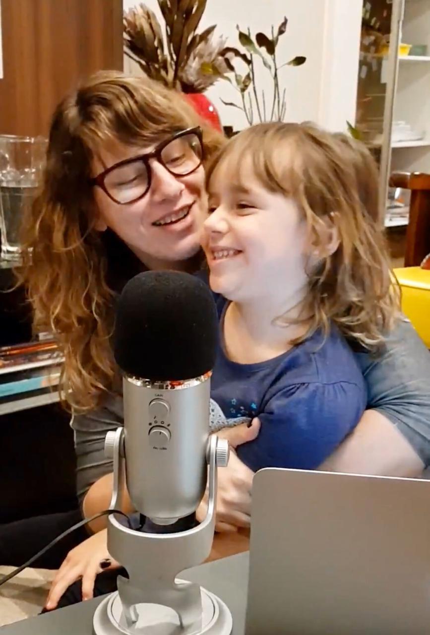 Tatiana segura Alice no colo, diante do microfone, e as duas sorriem