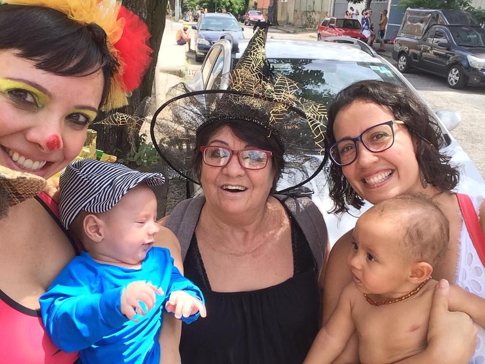 Cris aparece fantasiada, com Vicente no colo, ao lado de duas amigas, uma delas também segura um bebê