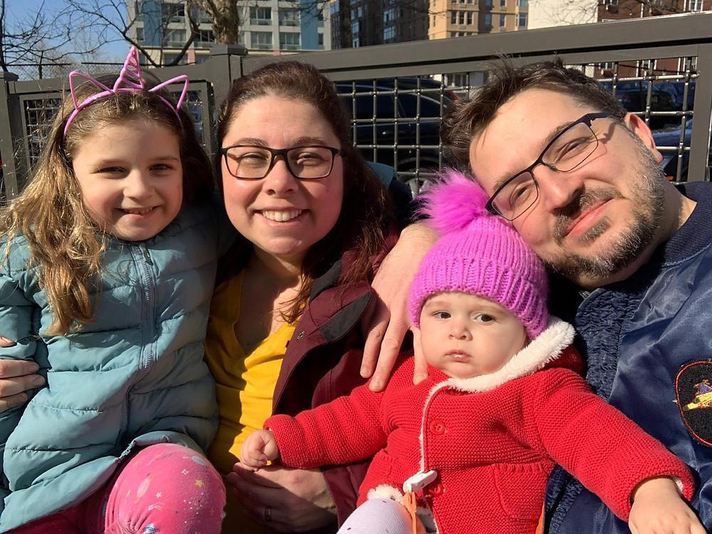 Ane, o marido e as filhas usam roupas de frio e gorros em uma rua de Nova York