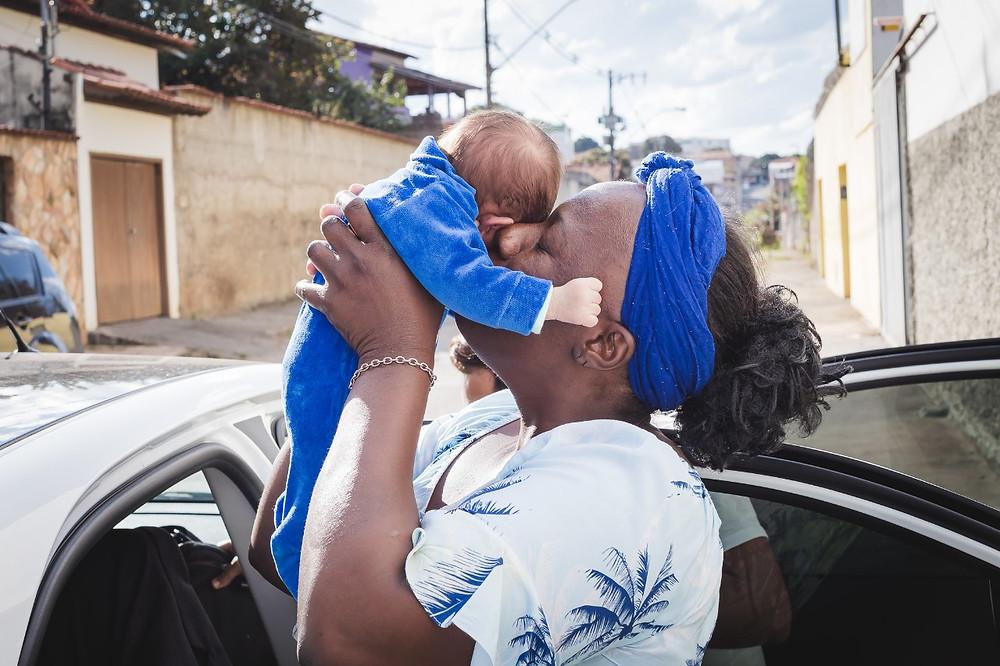Na porta do carro, Liliane segura Benício e beija o rostinho do bebê