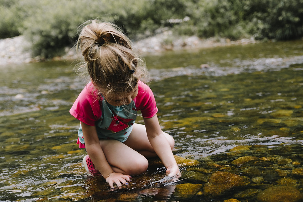 Garotinha brinca com as pedras do fundo de um riacho