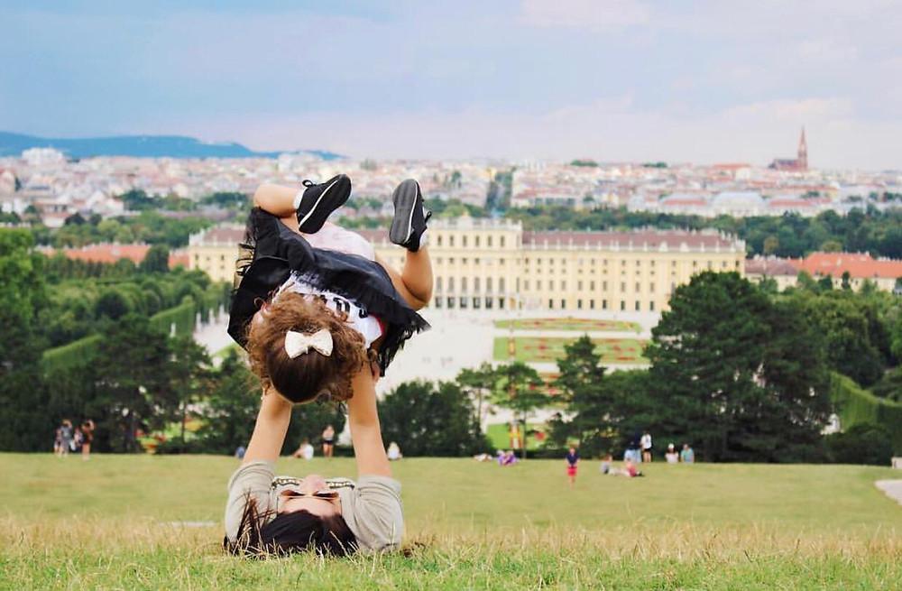Cristina está deitada na grama, levantando Malu com os braços. A menina tem um laço branco no cabeço e está com os pés para cima