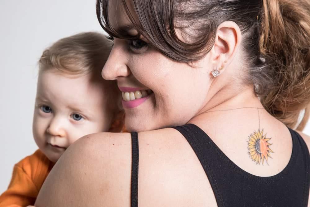 Flávia segura Larissa no colo e mostra uma tatuagem metade sol, metade girassol