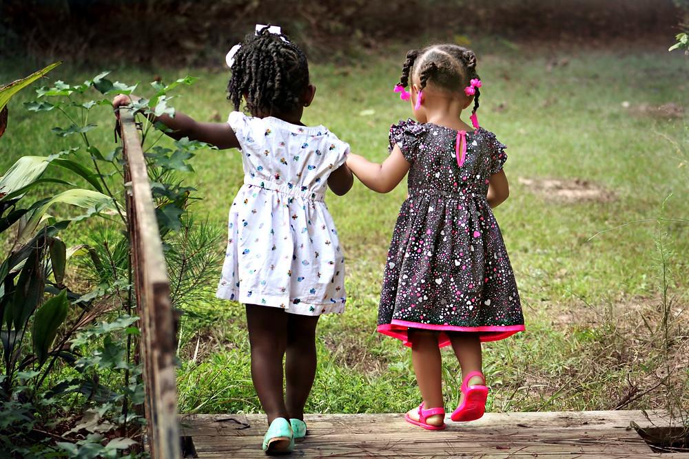 duas meninas pequenas, de vestidos coloridos, negras, atravessando uma ponte de mãos dadas