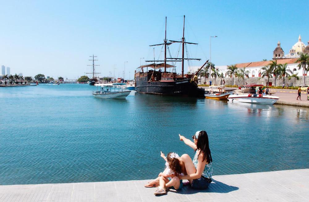 Mãe e filha estão de costas, sentadas em uma calçada diante do mar, apontando para os barcos