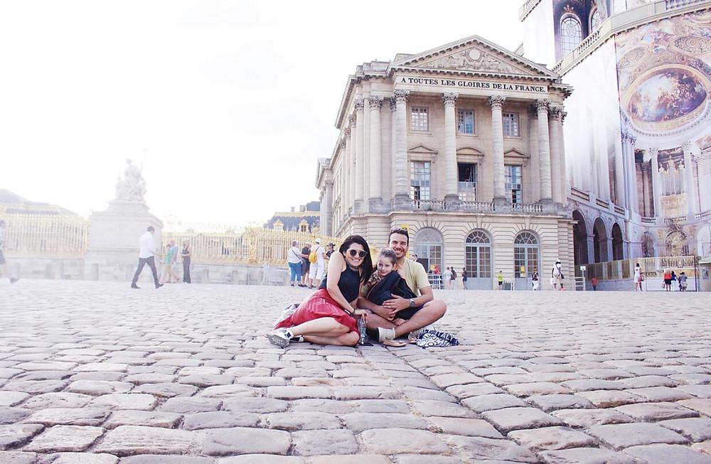 Malu está no colo de Alexandre e os três estão sentados no chão. Atrás deles está uma grande dourada que é a entrada do palácio de Versalhes