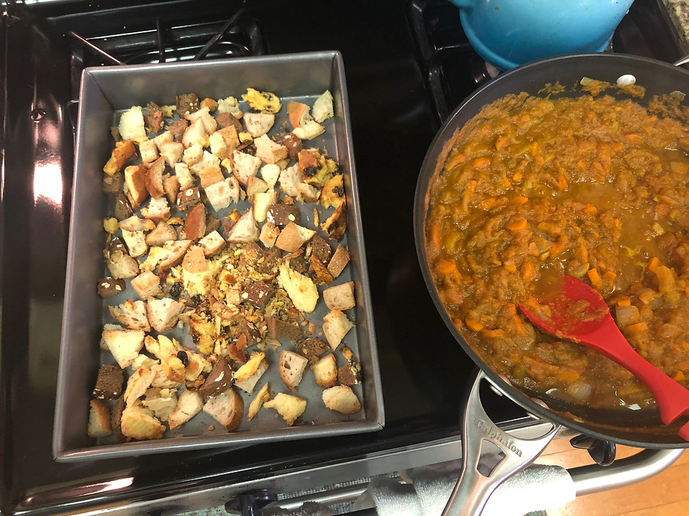 Bread scraps after drying out in a pan; next to veggies and pumpkins cooking on the stove