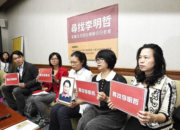 "Lee Ching-yu, , third right, the wife of Lee Ming-che, a missing Taiwanese human rights advocate and representatives of several non-governmental organizations call for help ascertaining Lee Ming-che's whereabouts at a news conference in Taipei yesterday. The signs say: ""Looking for Lee Ming-che."" Photo: Chen Chih-chu, Taipei Times"