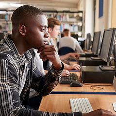 Male Student Working On Computer In Coll