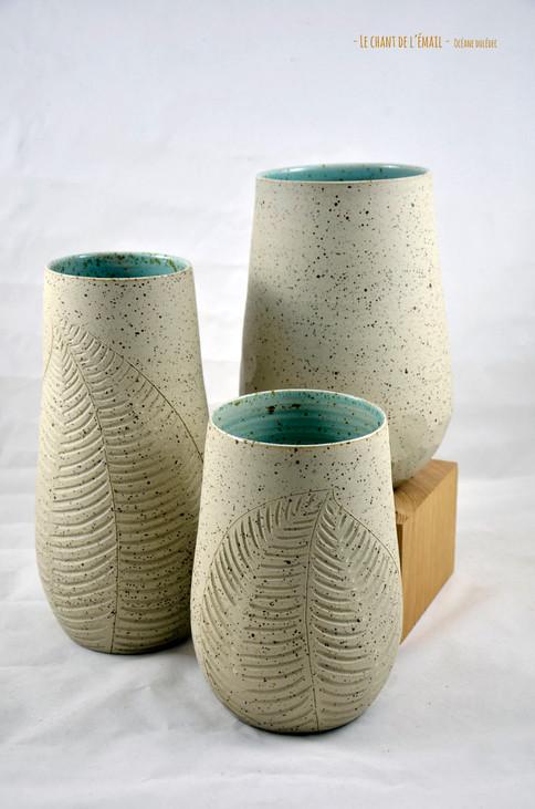 Vases en grès pyrité (moucheté) réalisé à la main dans mon atelier du Trièves. Motif végétal creusé dans la terre brute et émail vert d'eau  Dimensions variées de 20 à 40 cm (30 à 65 euros)