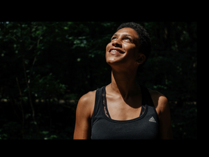 Photograph of a medium brown skinned woman with short, curly black hair in a black tank top with her face upturned towards the sun and a joyful smile against a dark background