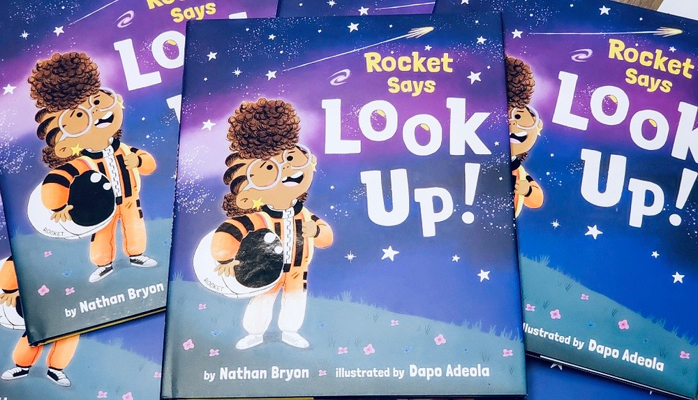 Photograph of a pile of copies of the book Rocket Says Look Up written by Nathan Bryon and illustrated by Dap Adeola