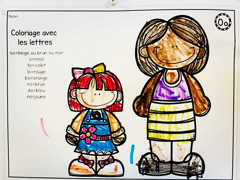 A colouring worksheet featuring one small person with red hair and light brown skin and one tall person with medium brown skin and dark hair both smiling