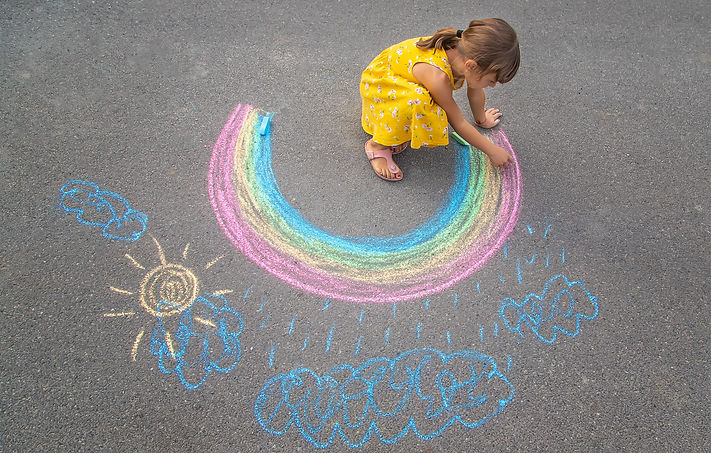 child-draws-rainbow-asphalt-selective-focus.jpg