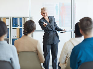 cheerful-business-coach-in-seminar-LF383