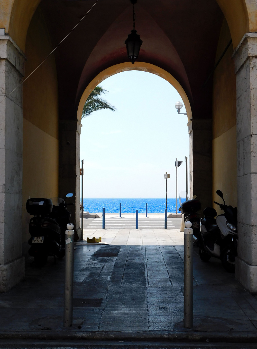 Blue ocean through ancient archway in Old Nice, France