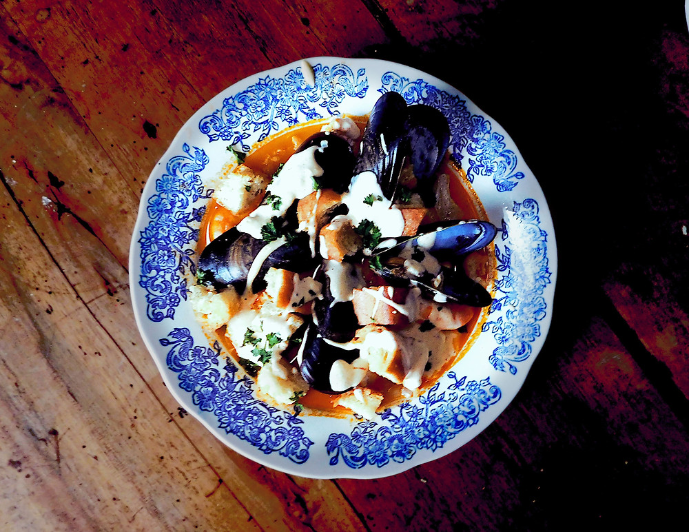 Colorful bowl of fish stew with mussels, shrimp, saffron, and orange broth