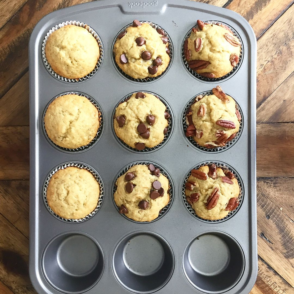 Muffin tray with plain, chocolate chip, and pecan banana bread on wooden table