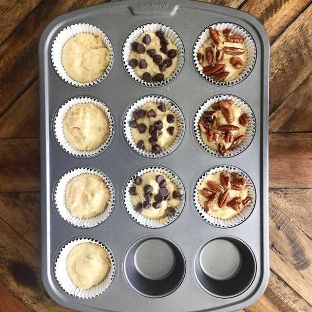 Muffin tray with plain, chocolate chip, and pecan banana bread batter on wooden table