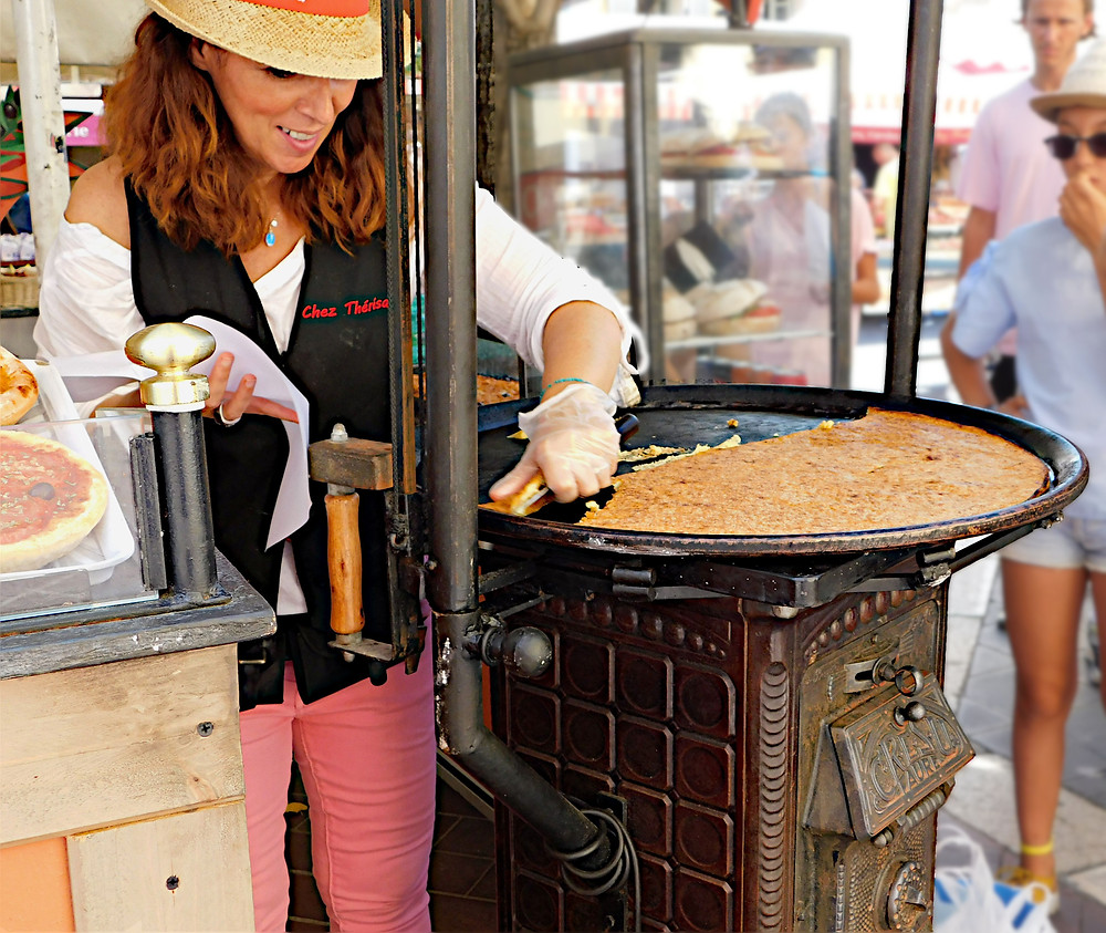 French woman in straw hat cutting crepe at French market