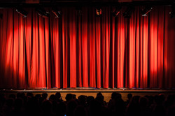 a closed red stage curtain in a small th