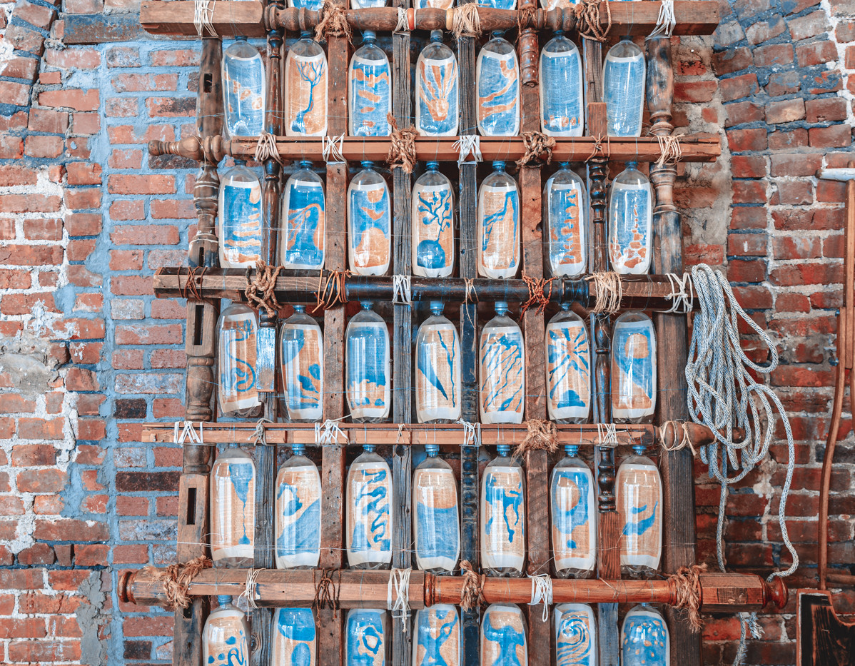 """JORDAN TIERNEY  """"Dream Boat"""" Found furniture parts, plastic bottles with maps inside, rope, and twine. The maps are painted on pages from A History of Ideas. The paddle is made of a crutch and a shutter. 104"""" x 53"""" x 6"""" 2015 NFS  Photograph by StereoVision"""