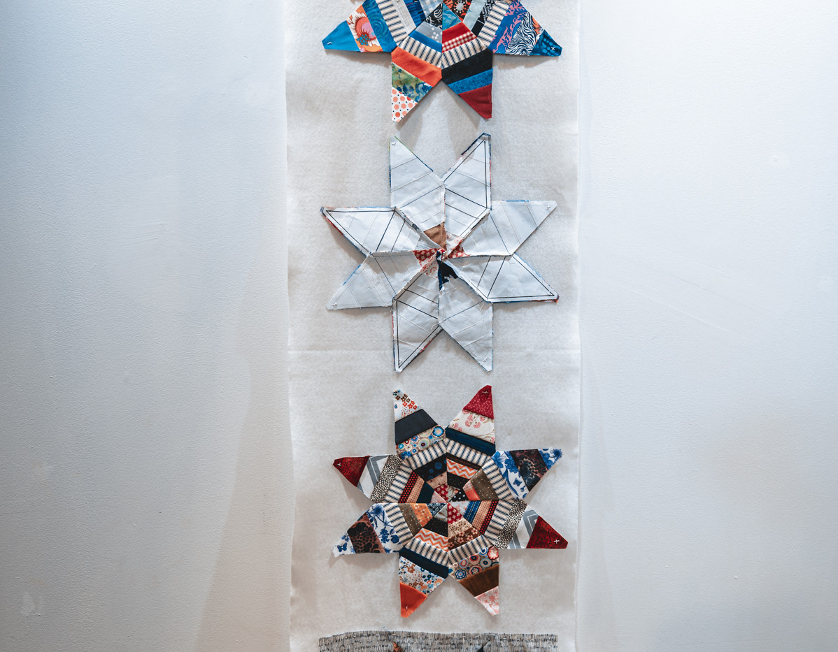 """FREDERICK NUNLEY  """"Eight Point Stars"""" Paper foundation with pieced cotton fabric scraps 18"""" x 71"""" 2020 NFS  Photograph by StereoVision"""