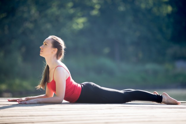 young woman in yoga pants and red shirt performing sphinx pose