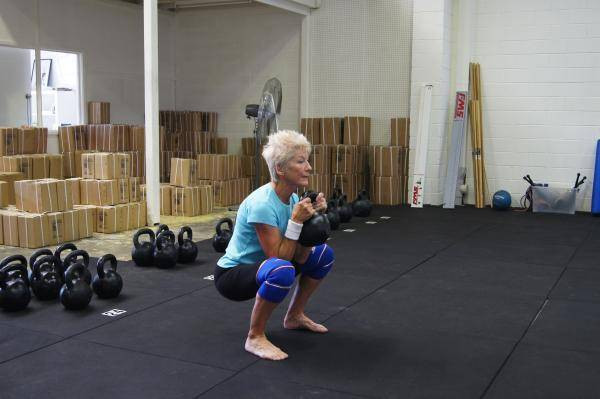 Older woman performing a perfect kettlebell front squat