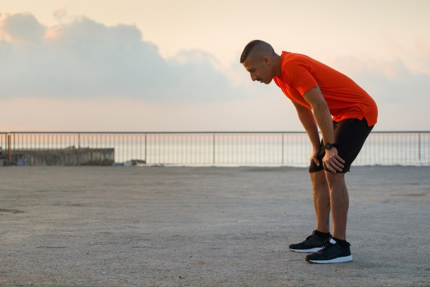 Man in orange shirt tired after run by the ocean