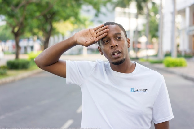 Man in white t-shirt wiping sweat from forehead