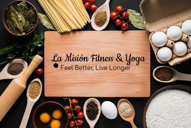 Cutting board surrounded by ingredients with La Mision Fitness & Yoga Motto