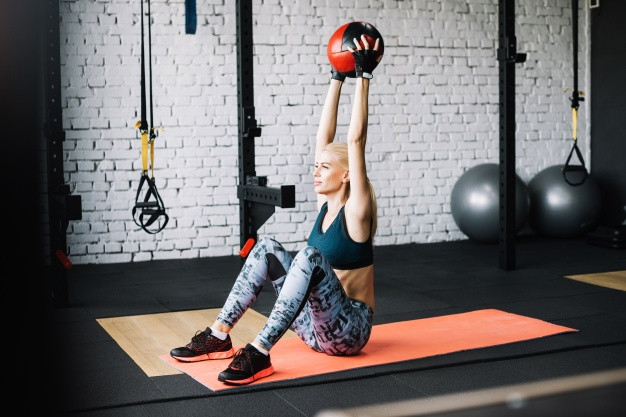 Young blonde woman in sports bra exercising with medicine ball
