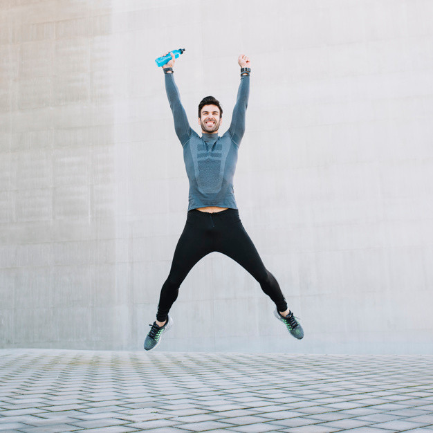 Man in blue shirt with blue water bottle jumping in the air with both arms overhead
