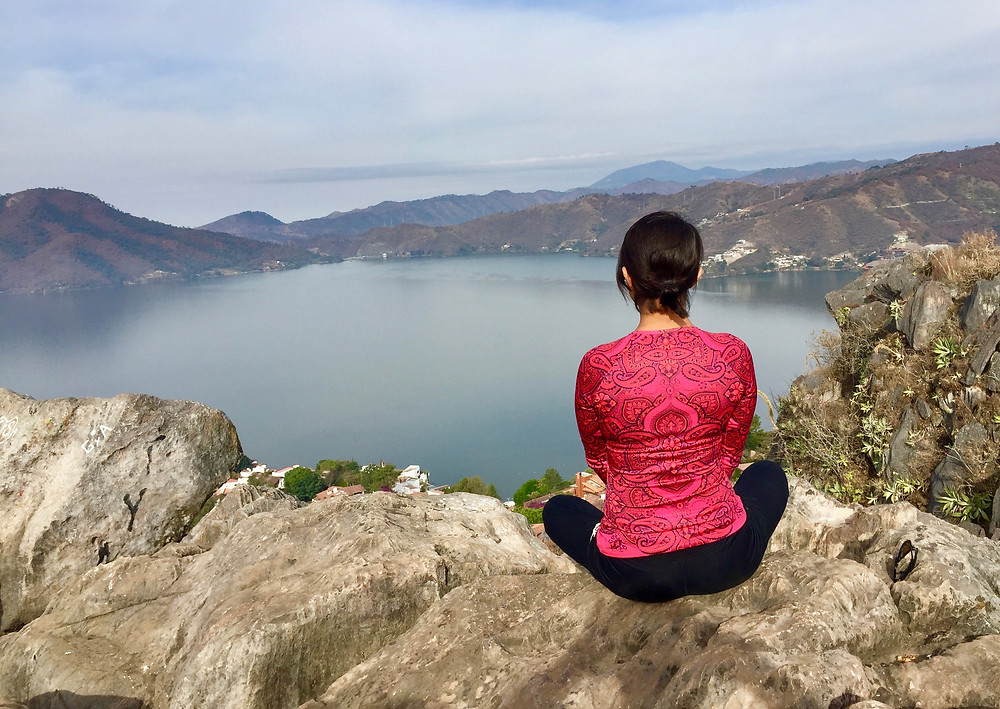 Young woman in red shirt looking out at beautiful lake