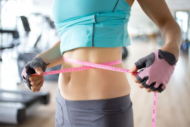 Skinny woman measuring her waist with pink tape measure
