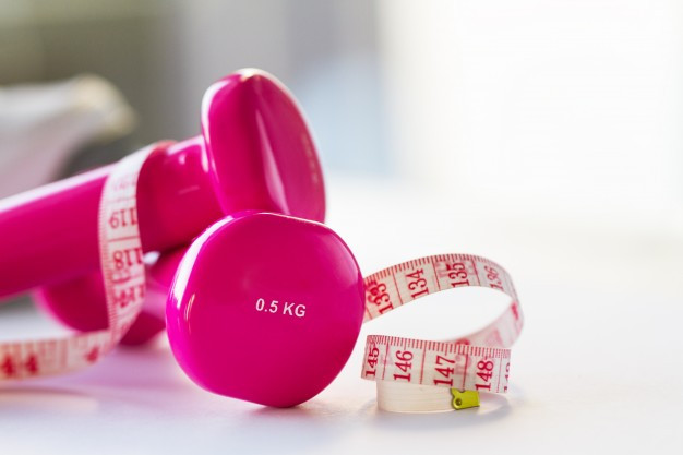 Pink .5 KG weights with tape measure and obscure background