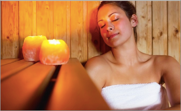 Young woman relaxing in candle lit sauna