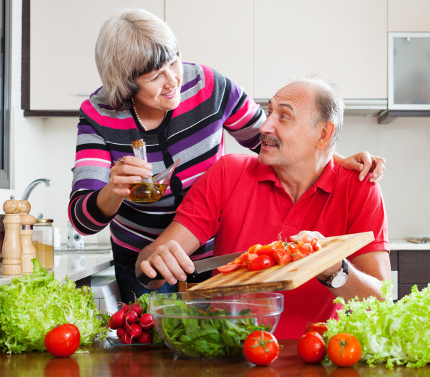 Older couple preparing a salad with cutting board